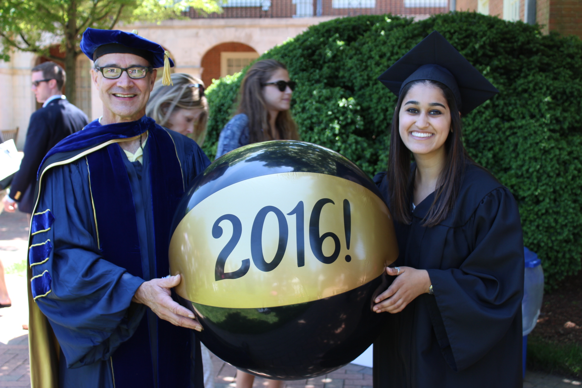 "Professor Luis González and students celebrating graduation, holding a large ""2016!"" black and gold beach ball"
